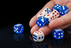 The male hand throwing dices on dark background. The male hand throwing colored dices on dark background Stock Photos