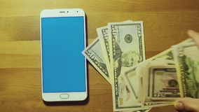 Male hand throws pile of banknote on srceen of white smartphone with blue key on wooden desk stock video footage