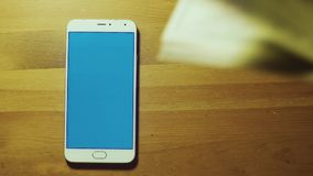 Male hand throws pile of dollars on srceen of white smartphone with blue key on wooden desk stock footage