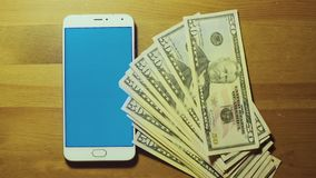 Male hand throws pile of dollars on srceen of white smartphone with blue key on wooden surface stock footage
