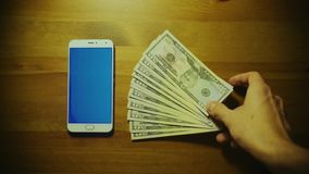 Male hand throws pile of dollars on srceen of white smartphone with blue key on wooden table stock video