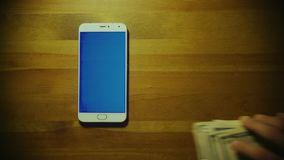 Male hand throws pile of money on srceen of white smartphone with blue key on wooden surface stock video footage