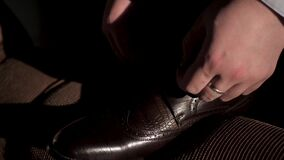 Male hand tie shoelaces. Caucasian man in white shirt and blue suit in dark room lace up shoes falling sunlight. Close. Male hand tie shoelaces. Caucasian man in stock video