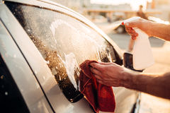 Male hand with tool for washing windows, car wash. Carwash station Royalty Free Stock Images