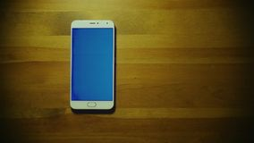Male hand touch screen and throws pile of dollars on srceen of white smartphone with blue key on wooden table stock footage