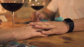 Male hand touching female hand while romantic date in evening restaurant. Woman touching hand girlfriend on table at. Evening dinner in elegant cafe. Romantic stock footage