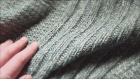 Male hand touching a smooth green sweater in a textiles shop. Close up shot.