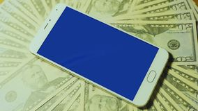 Male hand touching srceen of white smartphone with blue key display on pile of money stock video