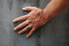 Male hand touching the surface of a concrete wall Royalty Free Stock Photo