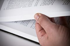 Male hand turning pages of a book Royalty Free Stock Image