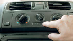 Male hand turning switch of car air conditioner Royalty Free Stock Photo