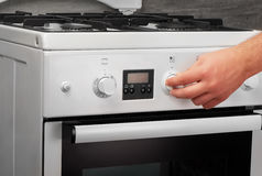 Male hand turning on white kitchen gas stove on gray stock image