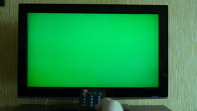 Male Hand With TV Remote Switching Channels On A Green Screen TV Point Of View stock video footage