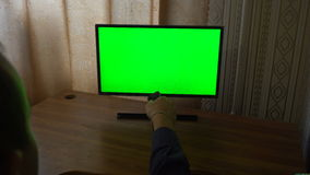 Male hand with tv remote switching channels on a green screen tv point of view stock video