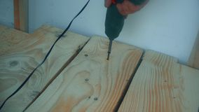 Male hand twist the screw into a wooden Board using a power screwdriver stock video footage