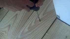 Male hand twist the screw into a wooden Board using a power screwdriver.  stock footage