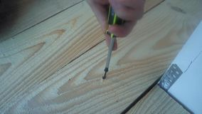 Male hand twist the screw into a wooden Board using a power screwdriver stock video