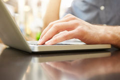 Male hand typing on laptop at outside cafe. Close up portrait of male hand typing on laptop at outside cafe Royalty Free Stock Image