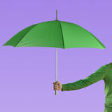 Male hand with umbrella. Male hand holding a green umbrella against a violet background Stock Photography