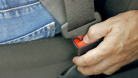 Male hand unfastening car safety seat belt Royalty Free Stock Image