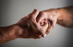 Male hand united in handshake. Man help hands, guardianship, protection. Two hands, arm, helping hand of a stock images