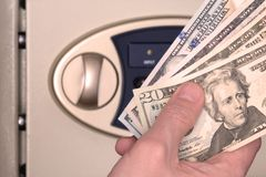 Male hand with US dollars on the background of the safe with the door open. The concept of saving money, service in a hotel or. Male hand with US dollars on the royalty free stock photo