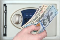Male hand with US dollars on the background of the safe with the door open. The concept of saving money, service in a hotel or. Male hand with US dollars on the royalty free stock images