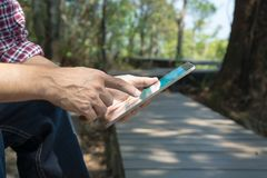 Male Hand use Digital Mobile Wireless Tablet PC in Forest Royalty Free Stock Photo