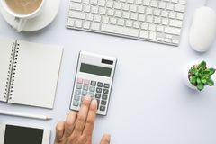 Male hand using calculator on office desk table with copy space. In white background.flat lay design Royalty Free Stock Image