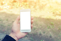 Male hand using mobile smartphone. And blurred background with vintage filter Royalty Free Stock Images