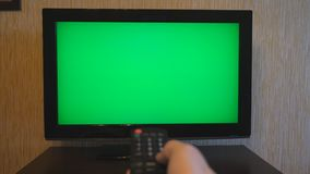 Male hand using a remote control to flipping channels on green screen TV. Arm of man surfing television channels with. Chroma key. Point of view of guy. POV stock footage