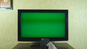 Male hand using a remote control to flipping channels on green screen TV. Arm of man surfing television channels with. Chroma key. Point of view of guy. POV stock video footage