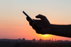 Male hand using smart phone at sunset. Close up silhouette of male hand using smart phone during sunset. City and buildings in the background. People and Royalty Free Stock Photography