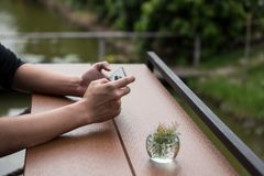 Male hand using smart phone. To chat, browse internet, play social media, check marketing e-commerce, or pay online banking with relax greenery outdoor Royalty Free Stock Photos