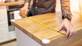 Male hand using tape measure on countertop. Male hand interior designer using tape measure for measuring size of wooden countertop in modern kitchen showroom in stock images