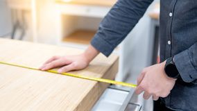 Male hand using tape measure on countertop. Male hand interior designer using tape measure for measuring size of wooden countertop in modern kitchen showroom in royalty free stock image