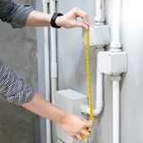 Male hand using tape measure on electrical conduit. Male hand electrician using tape measure for measuring dimension of electrical conduit and electrical box on royalty free stock photos
