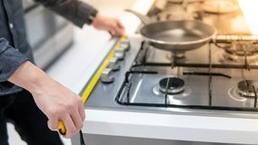 Male hand using tape measure on gas stove. Male hand interior designer using tape measure on gas stove on modern countertop in kitchen showroom. Shopping royalty free stock photo