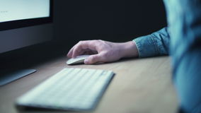 Male hand using wireless mouse and computer. At night stock footage