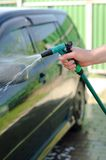 Male hand washes the car with a hose Stock Image
