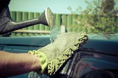 Male hand washes the car's hood Royalty Free Stock Image
