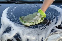 Male hand washes the car's hood from a watering can Stock Images