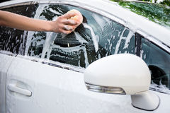 Male hand washing car with sponge. Male hand washing white car with sponge Stock Images