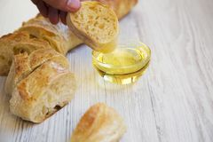 Male hand wetting italian baguette in oil, side view. Closeup Stock Photos