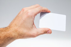 Male hand with white empty card over gray Royalty Free Stock Photography