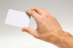 Male hand with white empty card over gray Royalty Free Stock Image