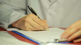 Male hand in a white lab coat writing pen in the documents. stock video footage