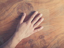Male hand on a wooden table Royalty Free Stock Image