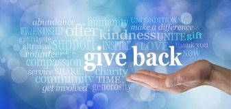 GIVE BACK word tag cloud. Male hand with the words GIVE BACK floating above surrounded by a word cloud against a blue bokeh background stock photography