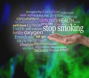 STOP SMOKING word tag cloud. Male hand with the words STOP SMOKING floating above surrounded by a relevant word cloud with a vibrant modern abstract background royalty free stock photo